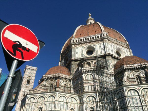 Florenz: Der Campanile, der Dom Santa Maria del Fiore mit der berühmten Kuppel und ein Straßenschild beklebt von Clet Abraham. Mai 2015. Foto © Welz