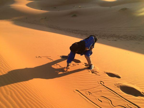 Erg Chebbi: Ein Wüstenbewohner, mein Begleiter, schreibt meinen Namen in den Sand. Foto © Welz