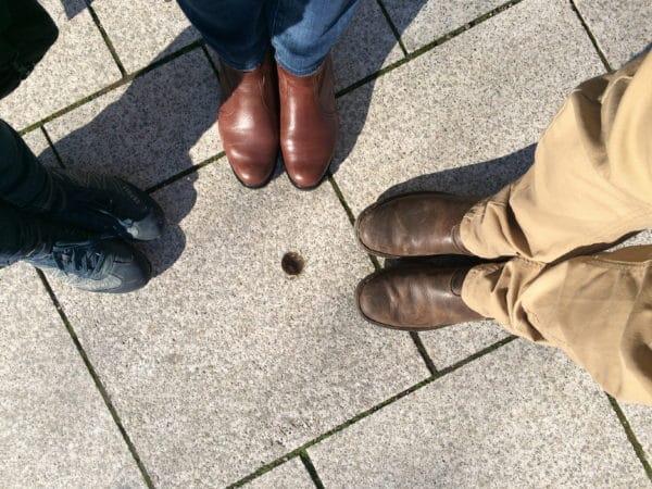"""Eva-Maria Bast, Jørn Precht und ich stehen um den Abendstern herum, ein einfaches """"Loch"""" in einer Gehwegplatte in der Stuttgarter Innenstadt. Foto © Welz"""